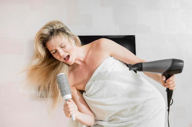 Frau, die ihre haarbürste als mikrofon benutzt