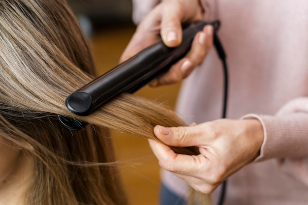 Frau, die ihre haare zu hause glättet