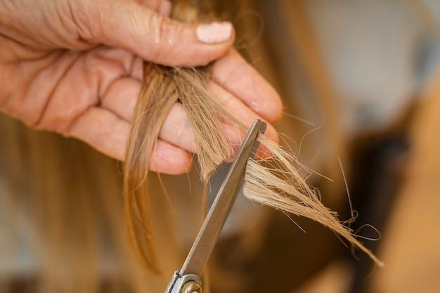Frau, die ihre haare zu hause vom friseur schneiden lässt