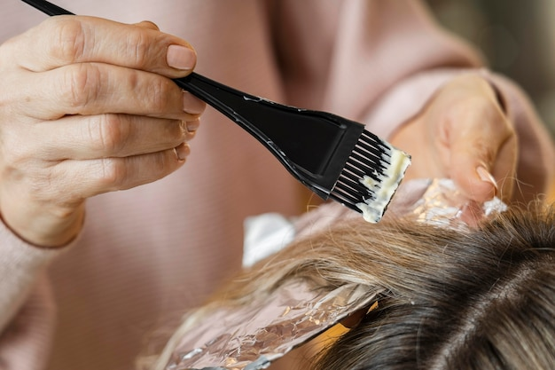 Frau, die ihre haare zu hause von kosmetikerin gefärbt bekommt