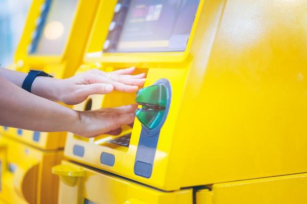 Frau, die ihre hände abdeckt, während sie ihre pin an einem geldautomaten eingibt