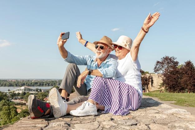 Frau, die ihre hände beim nehmen eines selfie anhebt