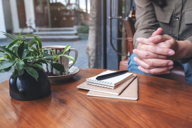 Frau, die ihre hände beim sitzen im haus mit notizbüchern, stift und kaffeetasse auf holztisch hält