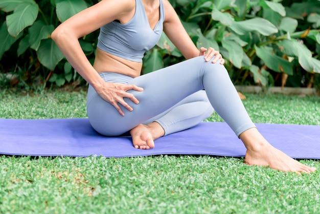 Frau, die ihre hände benutzt, um den oberschenkel zu massieren, um die muskeln nach ihrem training zu entspannen