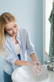 Frau, die ihre hände im badezimmer wäscht
