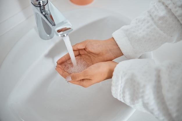 Frau, die ihre hände im waschbecken wäscht