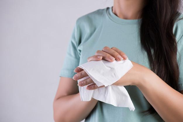 Frau, die ihre hände mit einem gewebe säubert