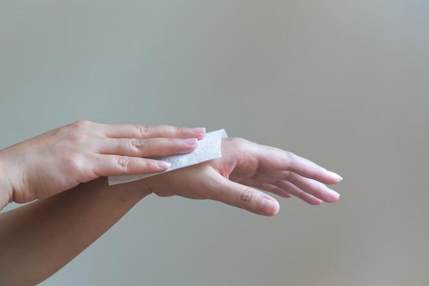 Frau, die ihre hände mit weißem weichem seidenpapier säubert isoliert auf weißem hintergrund