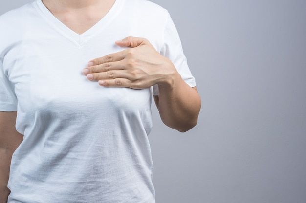 Frau, die ihre hand auf brust für das überprüfen des größen- oder krebsbewusstseins setzt