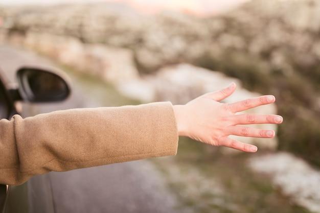 Frau, die ihre hand aus auto heraus nimmt
