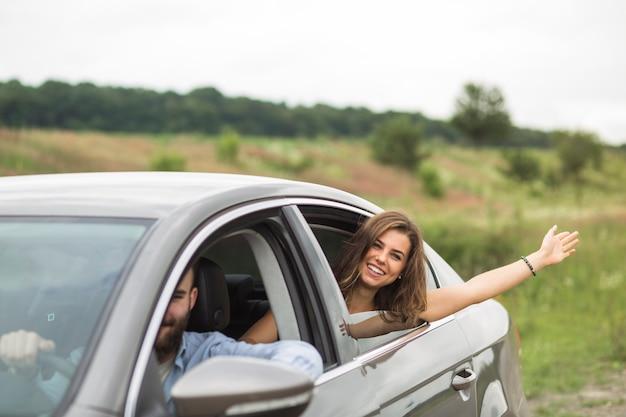 Frau, die ihre hand außerhalb des autofensters wellenartig bewegt