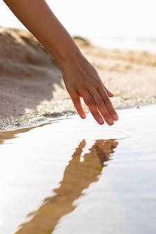 Frau, die ihre hand durch wasser am strand läuft