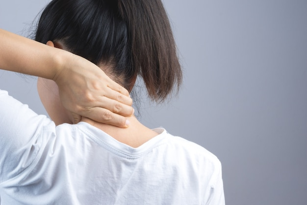 Frau, die ihre hand für nacken- oder dornschmerz setzt