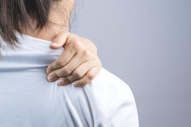 Frau, die ihre hand für nacken- und schulterschmerz setzt