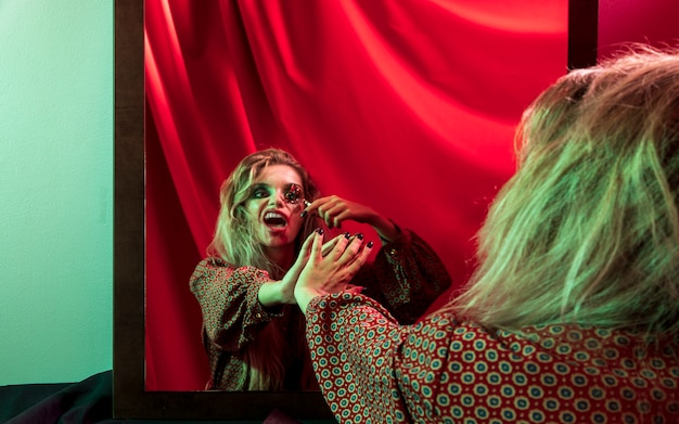Frau, die ihre hand im spiegel berührt