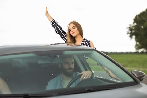 Frau, die ihre hand von außerhalb des autofensters wellenartig bewegt