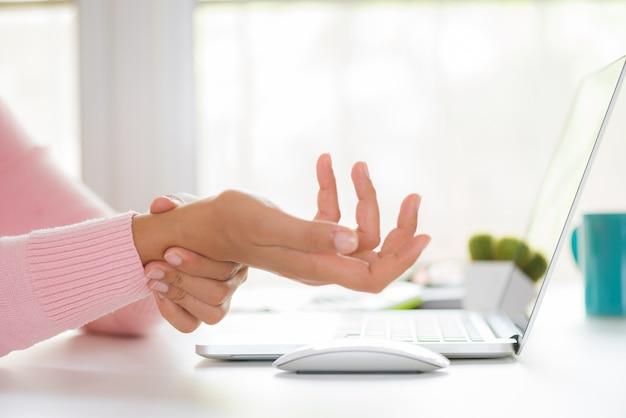 Frau, die ihre handgelenkschmerz von der anwendung des computers hält. büro-syndrom