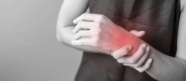 Frau, die ihre handgelenkschmerzen hält, weil sie lange zeit smartphone oder computer verwendet. de quervains sehnenscheidenentzündung, kreuzungssymptom, karpaltunnelsyndrom oder office-syndrom-konzept