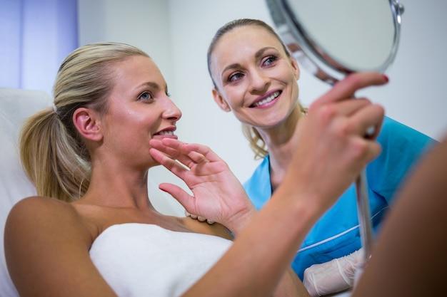 Frau, die ihre haut im spiegel prüft, nachdem sie kosmetische behandlung erhalten hat
