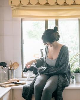 Frau, die ihre katze in der küche streicht