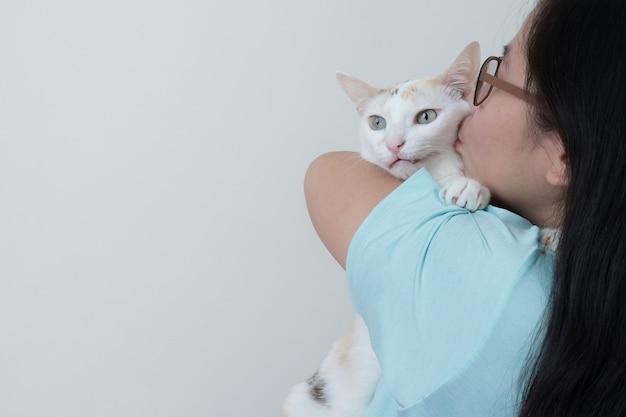 Frau, die ihre katze mit liebe umarmt und küsst