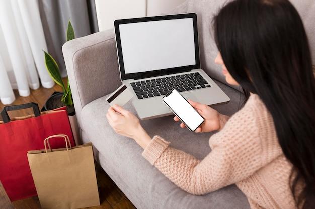 Frau, die ihre kreditkarte für einen neukauf benutzt