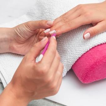 Frau, die ihre maniküre an der salon-nahaufnahme tut