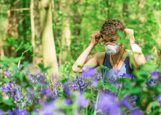 Frau, die ihre maske abnimmt und auf wiese zwischen glockenblumen im wald sitzt