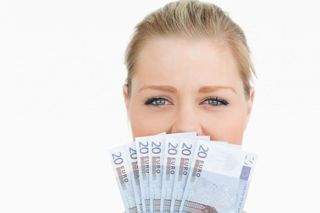 Frau, die ihre maus mit ihren eurobanknoten versteckt