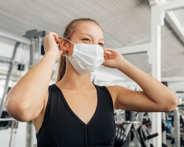 Frau, die ihre medizinische maske an der turnhalle aufsetzt