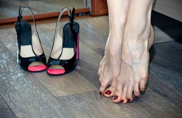 Frau, die ihre müden füße massiert