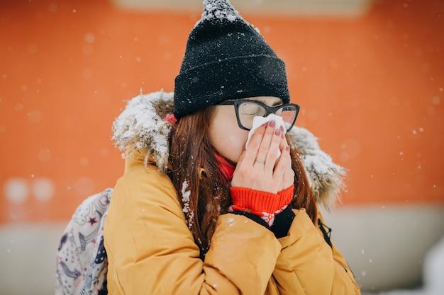 Frau, die ihre nase in taschentuch durchbrennt. junge frau, die mit grippe an einem wintertag krank wird