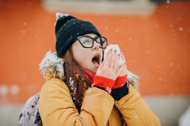 Frau, die ihre nase mit einem gewebe im freien im winter durchbrennt. junge frau, die mit grippe an einem wintertag krank wird