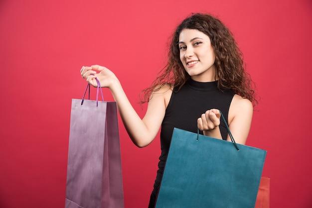 Frau, die ihre neuen kaufkleidung auf rotem hintergrund zeigt. hochwertiges foto