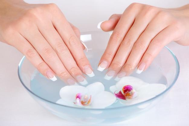 Frau, die ihre schönen finger mit wasser in die schüssel legt