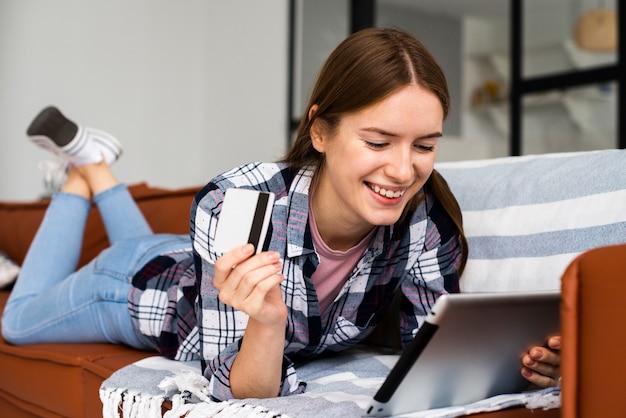 Frau, die ihre tablette betrachtet und eine kreditkarte hält