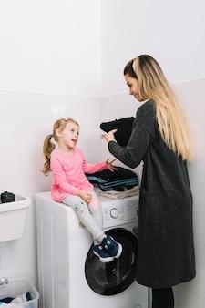 Frau, die ihre tochter sitzt auf waschmaschine betrachtet