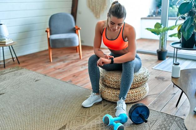 Frau, die ihre trainingszeit zu hause überprüft. konzept für sport, fitness, lifestyle, technologie und menschen - frau, die herzfrequenzuhr einstellt.