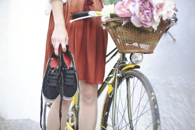 Frau, die ihre turnschuhe hält, während sie in der nähe ihres fahrrads steht