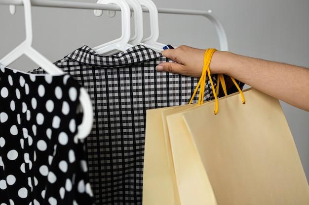 Frau, die ihre verkaufseinkaufskleidung auf gestell anordnet