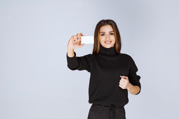 Frau, die ihre visitenkarte und faust zeigt, die auf ihren erfolg zeigt.
