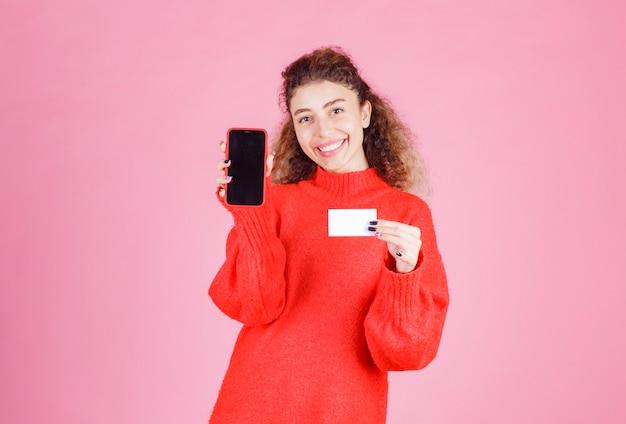 Frau, die ihre visitenkarte vorlegt und ihr telefon zeigt, um mit ihnen in kontakt zu treten.