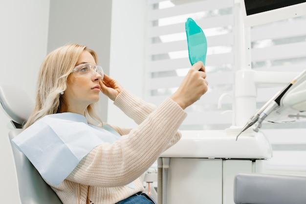 Frau, die ihre zähne betrachtet. lächelnde dame in der zahnarztpraxis.