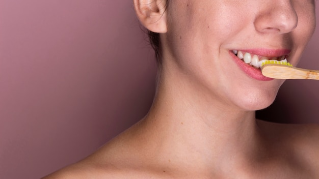Frau, die ihre zahnnahaufnahme putzt