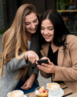 Frau, die ihrem freund etwas auf ihrem telefon zeigt