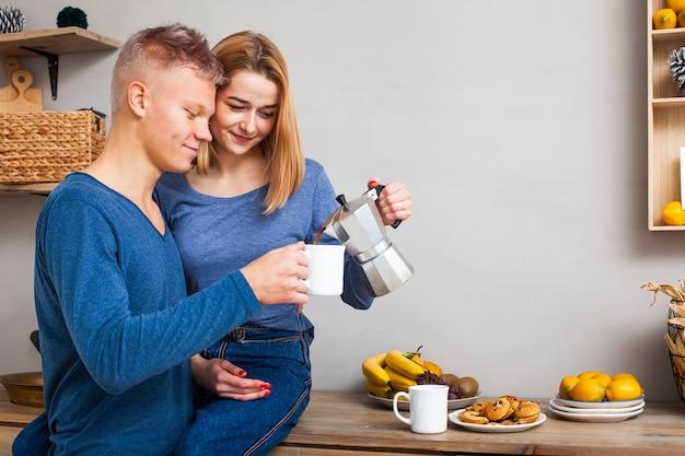 Frau, die ihrem freund etwas kaffee mit kopienraum gießt