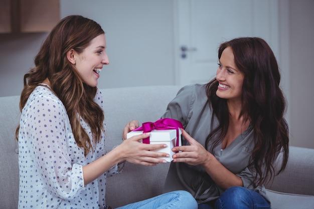 Frau, die ihrem freund im wohnzimmer ein geschenk gibt