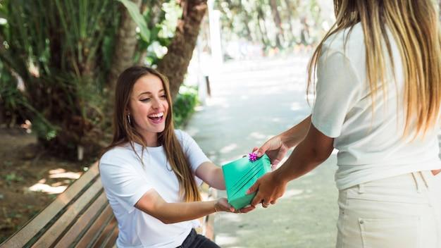 Frau, die ihrem glücklichen freund im park geschenk gibt