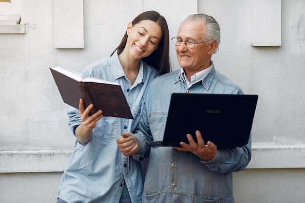 Frau, die ihrem großvater beibringt, wie man einen laptop benutzt