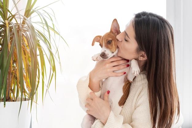 Frau, die ihrem niedlichen hund einen kuss gibt